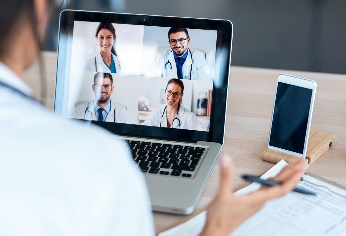 Female doctor talking with colleagues through a video call with a laptop in the consultation.
